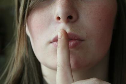 指で唇を押さえる女性