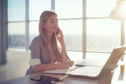 電話を掛けながらメモを取る女性