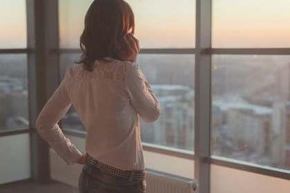 電話を片手に高層階の窓から外を見る女性の後ろ姿