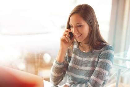 部屋で携帯を使い電話する女性画像