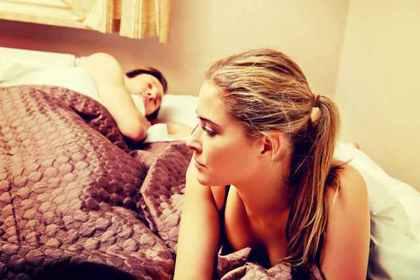 ベッドに寝る男性と悩む女性