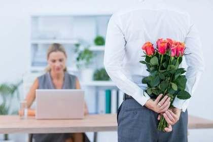 女性を前に花束を隠し持つ男性
