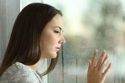 雨の日の窓際にいる女性