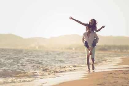 男性が女性を背負い笑顔で海岸を歩いているカップル