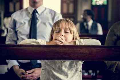 女の子が目を閉じて机に腕を載せて祈っている