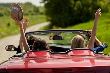 赤いオープンカーの女性二人