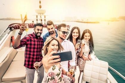 ヨットの上で写真を撮る男女