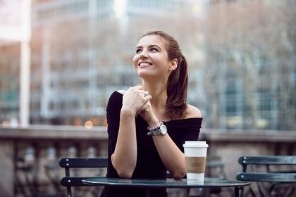 カフェのテラス席で笑顔で空を見上げている黒い服のポニーテールの女性