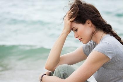 海辺で悲しみにくれる女性