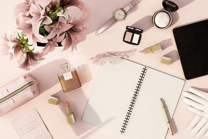 ユリの花束と広げられたノートやタブレット・化粧品などの小物