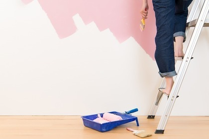 女性がハシゴに乗って白い壁をピンク色に塗っている足元だけ写っている