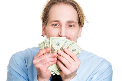 お金を抱きしめる男性