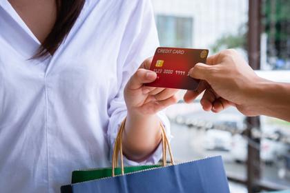 カードと紙袋を持つ女性