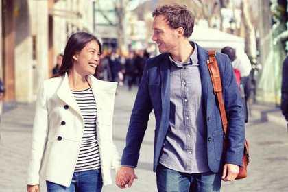 街で手をつなぎながら歩き、微笑みあう男女