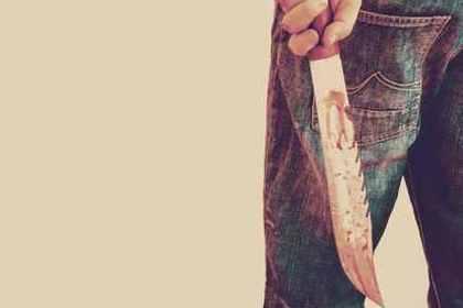 血のついた刃物を持つ男性