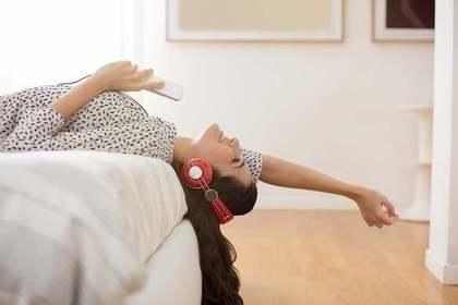 ベットの上で音楽を聴く女性