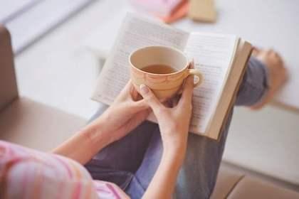 お茶を飲みながら読書する女性