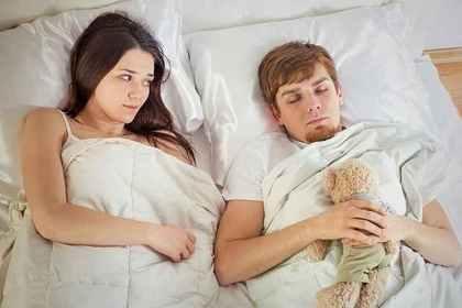 ぬいぐるみを抱いて眠る男性を困惑して見つめる女性