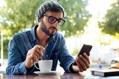カフェでコーヒーを飲みながらスマホを見る男性