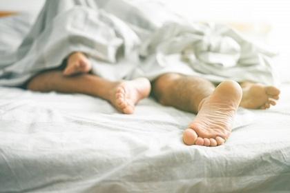 男女のベッドの上での足の画像