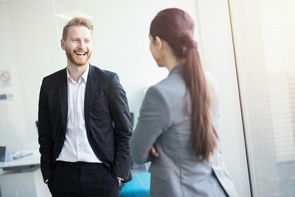 職場で笑顔で話す男女