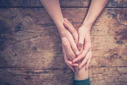 男性の手を握る女性