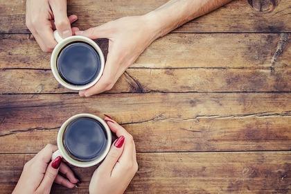 コーヒーカップを持って向き合う男女の手