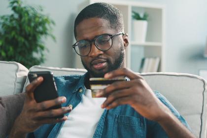 コーヒーを飲みながらスマホを触る男性