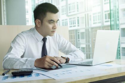 白いノートパソコンを使う男性