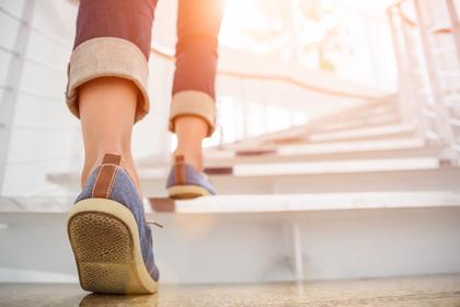 スニーカーで階段を上る画像